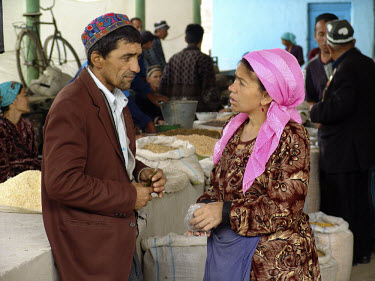A man and woman have a discussion at the marketplace.