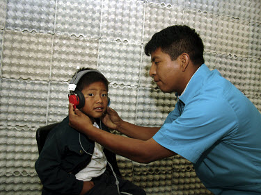 A technician tests a child's hearing at a health clinic.