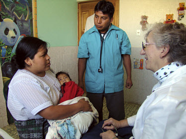 Nurse Liz Remily (right) attends to patients at her clinic.