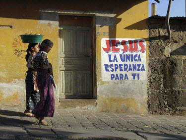 "Women walk past a sign which reads ""Jesus is the only hope for you!"""