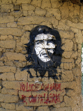 Graffiti depicting Che Guevara, painted onto a rough wall.