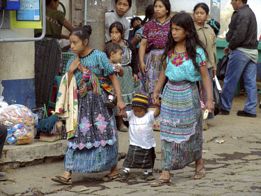 Woman and children in Mayan dress walk through the weekly Mayan market.