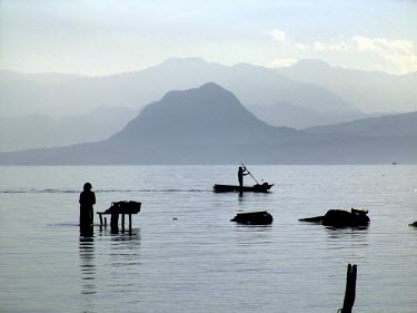 A woman washes clothes in Lake Atitlan while a man paddles past in a canoe.