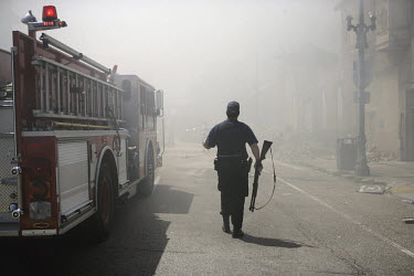 FDNY firemen from New York join local crews to fight fires started deliberately during the state of anarchy which followed Hurricane Katrina. The firemen are protected by armed guards as they have bee...