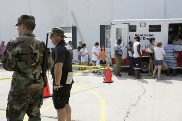 Residents of Covington queue for supplies at a Red Cross aid station. Soldiers and armed police monitor proceedings to prevent violence. The town was flooded in the aftermath of Hurricane Katrina.