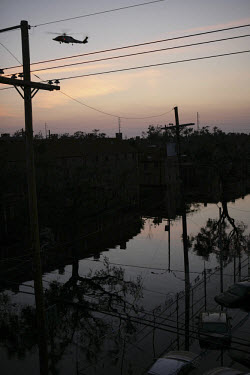 A flooded New Orleans street at sunset in the aftermath of Hurricane Katrina. Helicopters buzz constantly overhead searching for survivors.