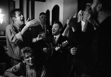 Musicians play instruments and sing in a bar during wedding celebrations.