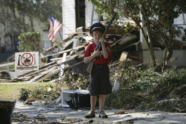 Eight year old Henry Loper guards his house from looters in the aftermath of Hurricane Katrina.