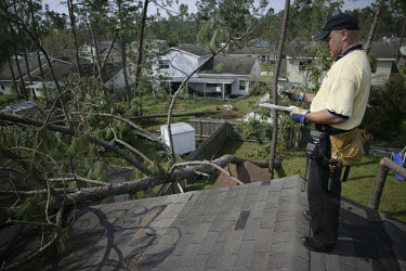 Loss Adjuster Marco Berard checking and assessing the damage caused by Hurricane Katrina for insurance claims on domestic property.
