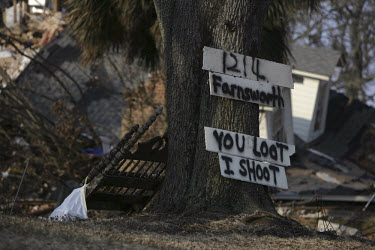 ^You loot I shoot^ - a sign pinned to a tree outside a home which was abandoned by its owners when Hurricane Katrina struck the Gulf Coast.