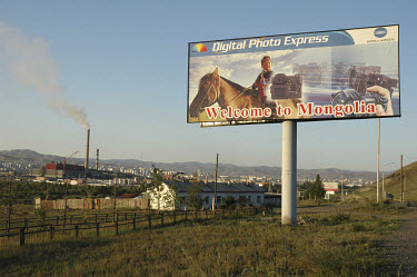 A sign on the outskirts of the city advertises Konica Minolta photographic equipment and reads 'Welcome to Mongolia'.