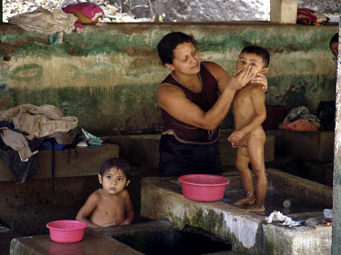 A woman at a communal washing house gives her children a bath.