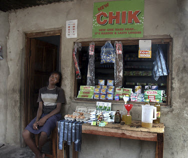 A woman sits outside a small shop at a market.