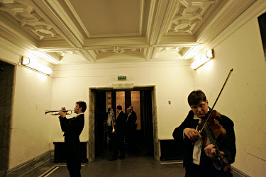 Musicians warm up backstage with their instruments; a violin and trumpets, before the concert at the Congress Hall in the Soviet-built Palace of Culture.