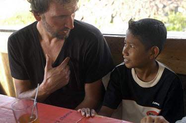 Actor Christopher Ecclestone visiting Aceh with the British Red Cross to raise awareness of the problems faced by people affected by the tsunami which struck this community a year earlier. In the vill...