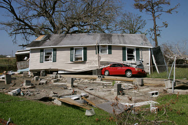 A wooden house, torn from its foundations and blown onto a car by Hurricane Katrina.  The hurricane struck the Gulf Coast in August 2005, causing an estimated $75 billion in damages and becoming the c...