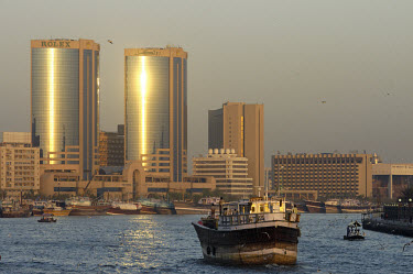 A dhow arrives to dock in the Dubai Creek, overlooked by the Rolex headquarters and Deira skyscrapers. A dhow is a traditional Arab sailing vessel used to transport freight.