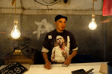 A youth wearing a T-shirt with the image of rap singer Eminem, works at a fish stall in the central market.