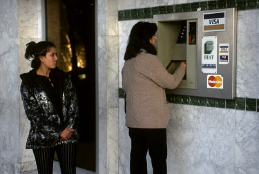 Woman usig an ATM bank machine, which accepts Visa and Mastercard.