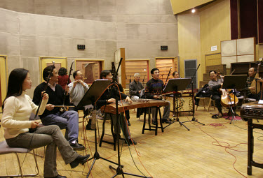 Musicians tune their instruments in a recording studio in preparation for the recording of the theme tune for the 'Market Place' American Public Media programme.