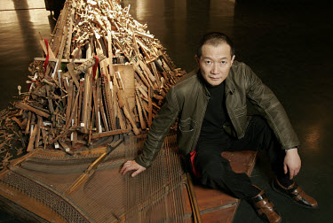 Artist, musician and composer Tan Dun, sitting next to his artistic installation work comprising wooden pieces of musical instruments.