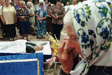 An elderly woman mourns a dead relative at a funeral.
