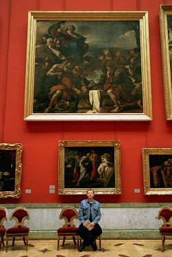 Visitor sitting in a hall with paintings at the Hermitage Museum.