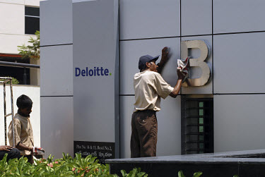 A caretaker cleans the sign on entrance to the headquarters of the accountancy firm Deloitte Touche Tohmatsu in Hyderabad Information Technology Engineering Consultancy City (HITEC City).  Successfull...
