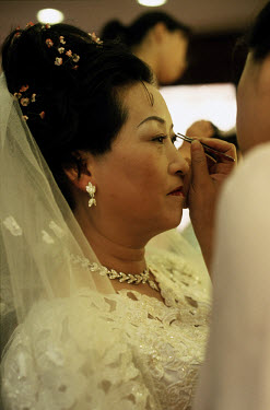A woman in a bridal gown has her make up applied in preparation for a photoshoot at the Twilight Red wedding photography studio.  After over thirty years of marriage, couples have come to the studio t...