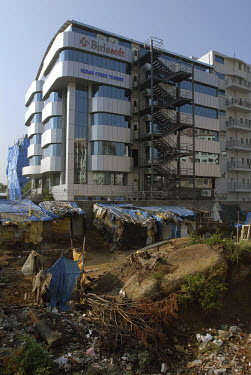A slum camp overlooked by the modern building for Birlasoft technology in Hyderabad Information Technology Engineering Consultancy City (HITEC City).  The camp is inhabited by construction workers and...