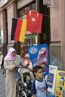 A Muslim woman and children pass a Turkish shop with German and Turkish flags in the Kreuzberg district during the 2006 football World Cup. Kreuzberg has a large Turkish immigrant population, many of...