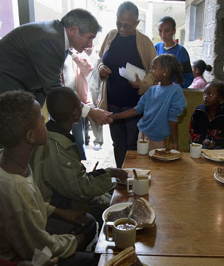Paul Wolfowitz, World Bank President, greets a child during a visit to IHA-UDP, a local NGO run by Dr. Jember Teferra (centre).