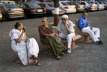 Elderly people sitting on the promenade of Marine Drive in the coastal district.