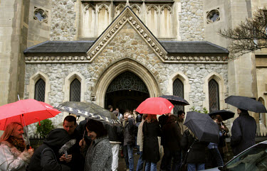 Polish immigrants stand under umbrellas outside a catholic church in Angel, North London.  The parish of this Polish church has grown from 300 families to 1300 families in only one year.