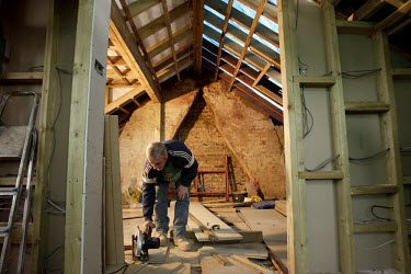 Polish construction worker Jerzy cuts boards with a circular saw in the loft of a housing renovation site.  Since Poland became a member of the EU (European Union) in 2004, thousands of Poles have arr...