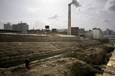 Man walking over the wasteland around a chemical factory, which dumps its waste into the Yellow River.