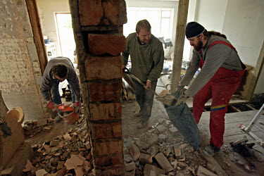 Polish construction workers shovel masonry during the renovation of a flat in Hanwell.  Since Poland became a member of the EU (European Union) in 2004, thousands of Poles have arrived in the UK to wo...