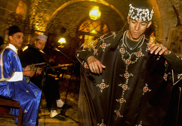 Musicians from the Gnawa (Gnaoua) ethnic group play instruments and dance to traditional music at the Mechouar club.