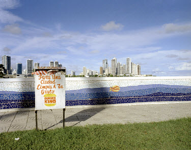 A rubbish bin sponsored by Burger King, with the skyscrapers of Panama City in the background.
