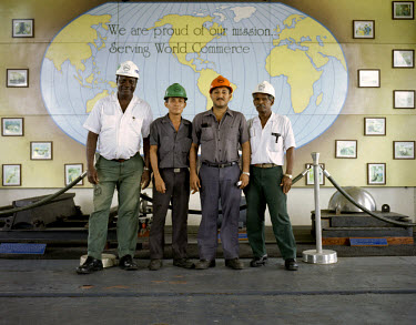Four workers at the Miraflores lock of the Panama Canal, in front of a map of the world proclaiming their mission to serve global commerce and trade.