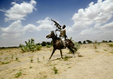 A Janjaweed militiaman on horseback close to the Chadian border. The Janjaweed (loosely translated as 'devils on horseback') have been terrorising the native population of Darfur since 2003.