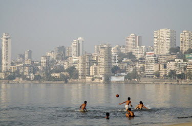 Boys play tag with a ball while swimming in the waters off Chowpatty Beach.