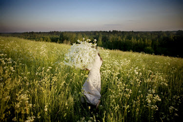 A young girl collecting flowers on a hilltop in the countryside near Piltinkalns. The flowers will be used as hair decoration during the pagan Midsummer Festival. The celebrations, which mark the long...