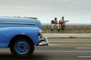 A car passes two musicians with guitars playing their instruments on Havana's Malecon waterfront promenade.