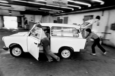 Female workers pushing a Trabant car at the VEB Sachsenring Automobilwerke factory. VEB Sachsenring, an East German car manufacturer, ceased production of its iconic Trabant at the end of 1991.