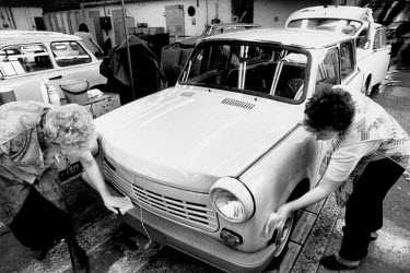 Female labourers working on the production of the last few Trabant cars at the VEB Sachsenring Automobilwerke factory. VEB Sachsenring, an East German car manufacturer, ceased production of its iconic...