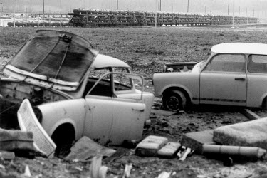 Wrecked Trabant cars next to a Volkswagen (VW) factory on the former VEB Sachsenring Automobilwerke production site of the Trabant car. The freight train in the background is carrying new VW Golf cars...