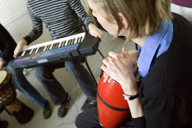 Patients playing a keyboard and other musical instruments during music therapy in a psychiatric clinic.
