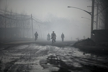 Cyclists make their way through a polluted haze in China's city of Linfen, in Shanxi province. A 2003 report by China's State Environmental Protection Administration (SEPA) indicated that Linfen is th...