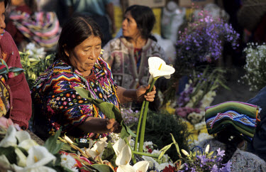 A Maya woman selling flowers on the steps of the Santo Tomas Catholic Church.